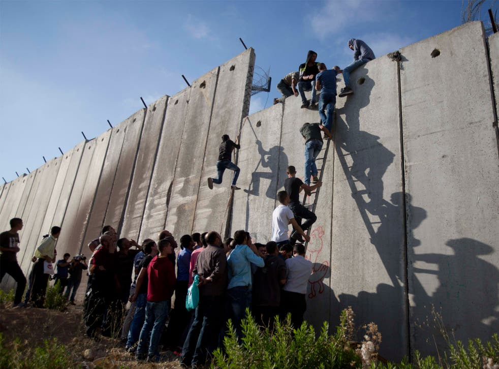 Palestinians use a ladder to climb over the separation barrier with Israel on their way to pray at the Al-Aqsa Mosque on the third Friday of the Muslim holy month of Ramadan, in Al-Ram, north of Jerusalem, Friday, 26 June 2015