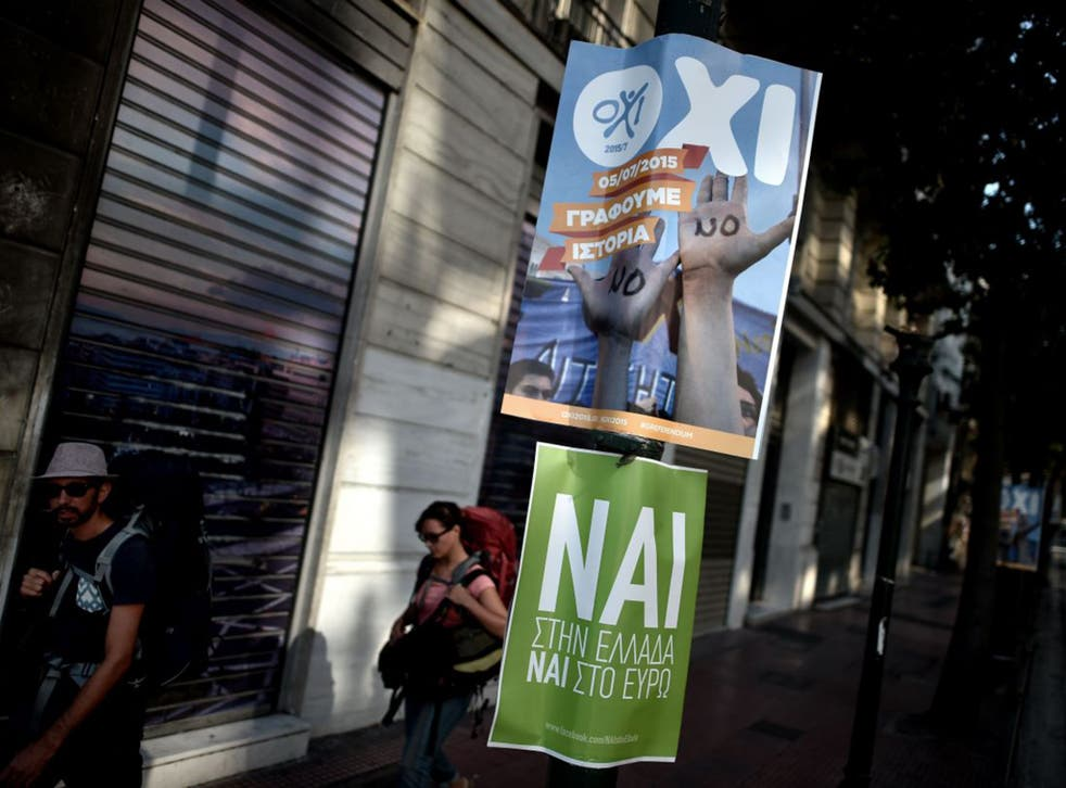 """Tourists walk past posters with slogans that read """"OXI"""" (NO) and """"NAI"""" (YES) ahead of the referendum in Athens on Sunday."""