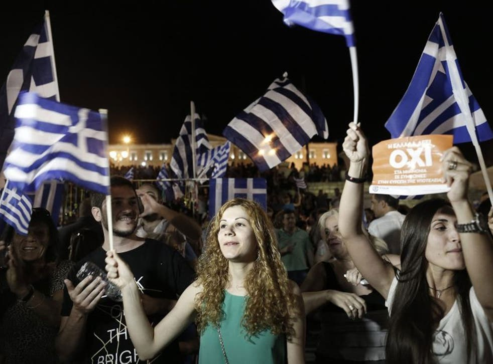 Supporters of the 'No' campaign wave flags and react after the first results of the referendum at Syntagma Square, in Athens