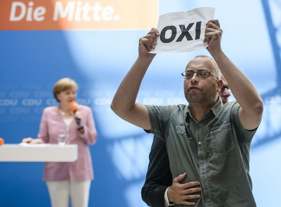 A protester holds a sheet with the Greek word for 'No' during an open house presentation of Germany's conservative Christian Democratic Union (CDU) party at Konrad Adenauer House