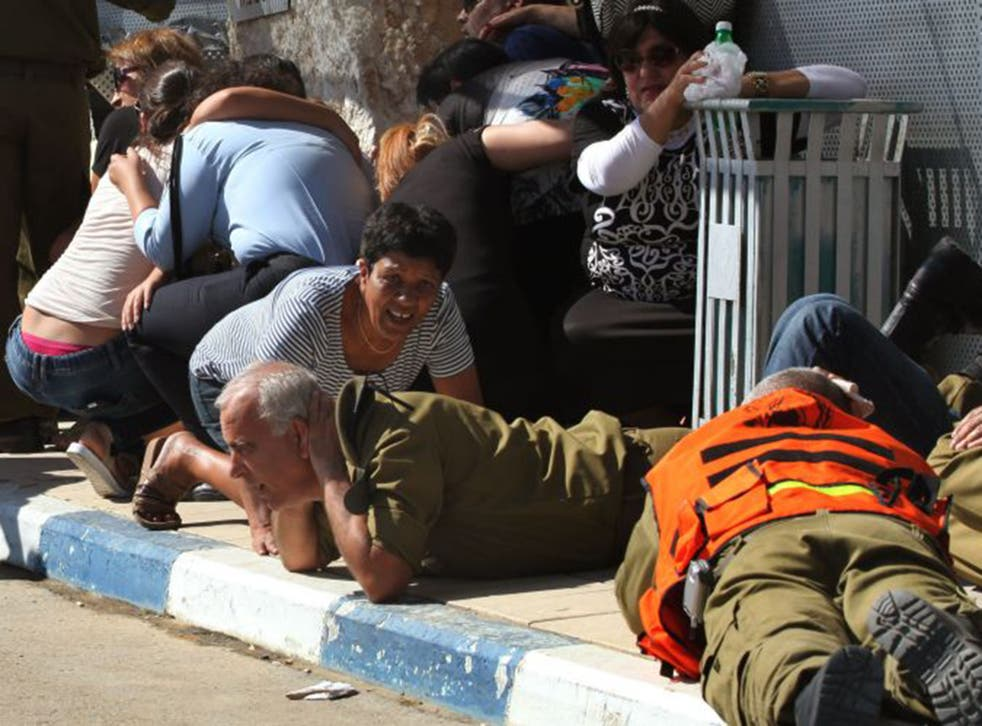 Israelis take cover from a rocket attack from Palestinian militants on the Gaza Strip during the funeral last July of Israeli soldier Corporal Meidan Maymon Biton, 20, killed in a mortar attack