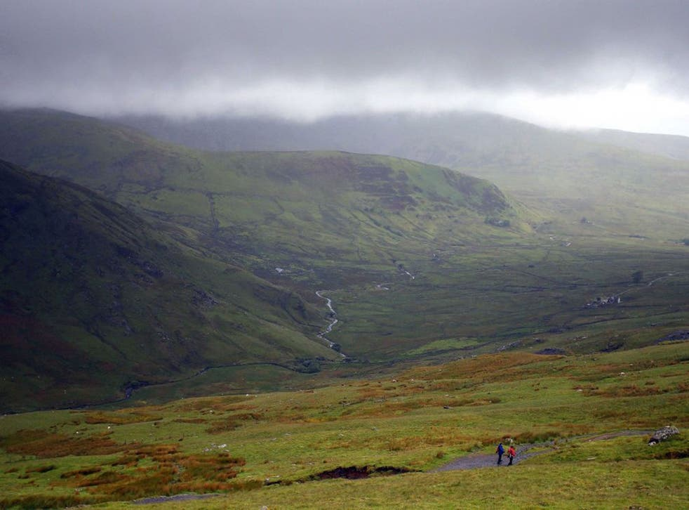 Walkers climb down Mount Snowdon in Snowdonia, north Wales, as two people died after they were hit by lightning while out walking as summer thunderstorms battered Britain.
