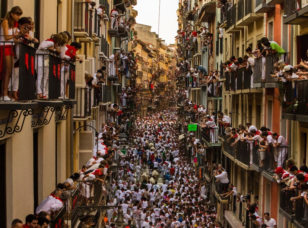 People watch as Jandilla fighting bulls and revelers run during the running of the bulls at the San Fermin festival in Pamplona, Spain