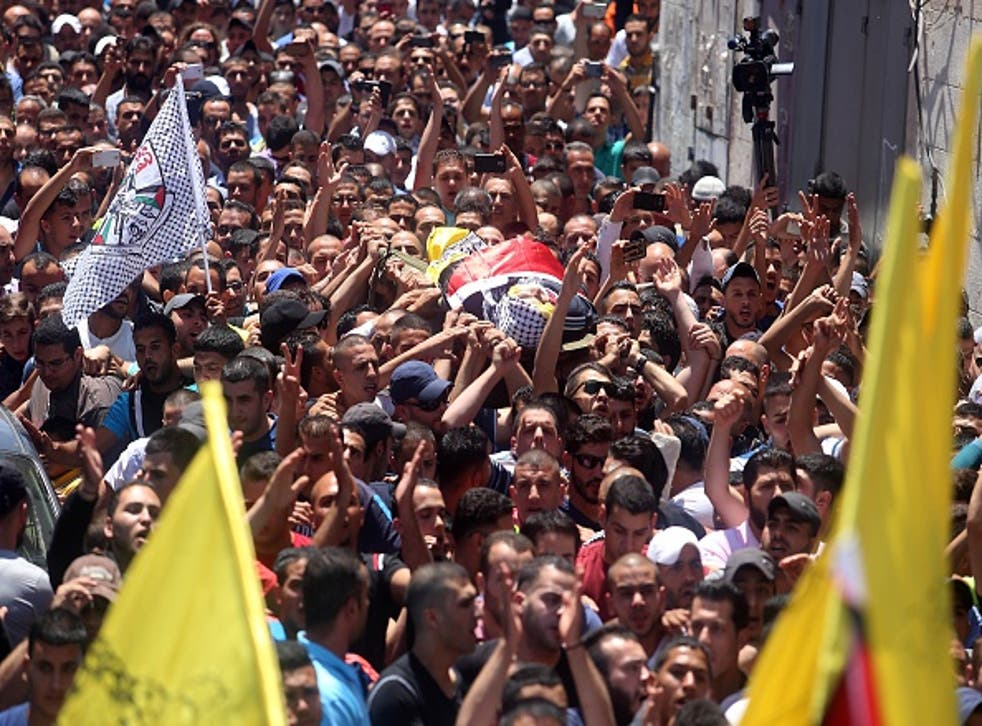 Hundreds of mourners escort the body of Muhammad al-Kasbeh at a funeral ceremony on July 3 in Ramallah