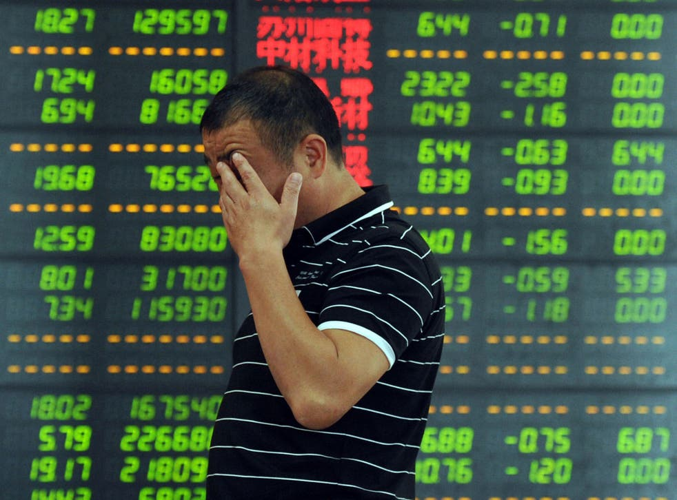 An investor reacts in front of a screen showing stock market movements in Fuyang, eastern China's Anhui province.