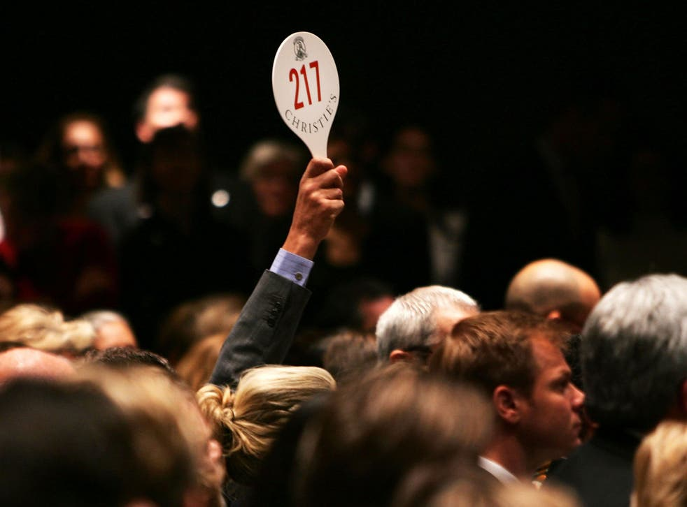 A man bids at an auction at Christie's in New York, which was not involved in the French scandal