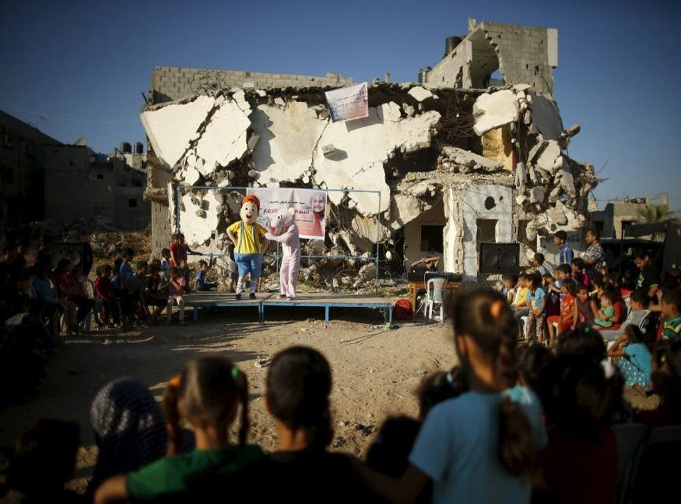 Children watch a performance in the ruins of a house destroyed by Israeli shelling during Operation Protective Edge