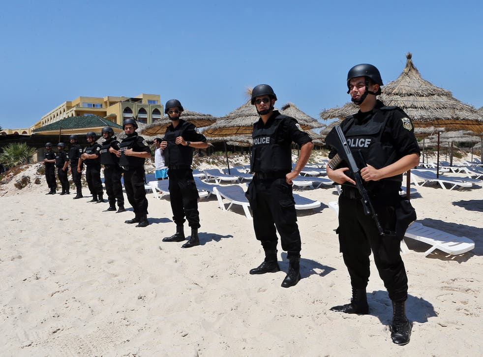 Members of the Tunisian security services stand guard during a memorial ceremony and minutes silence for the victims of a terror attack on a beach outside the Imperial Marhaba Hotel, in the popular tourist resort of al-Sousse, Tunisia