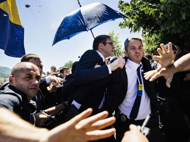Aides attempt to screen premier Aleksander Vucic as the missiles rain in