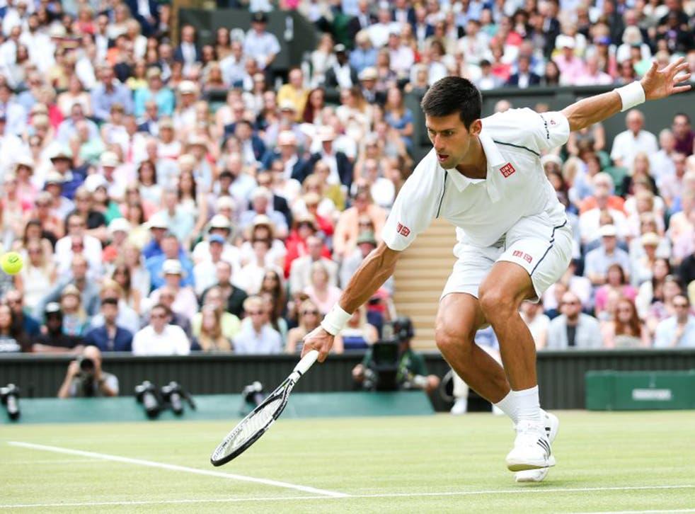 Novak Djokovic reaches low to make a return against Roger Federer