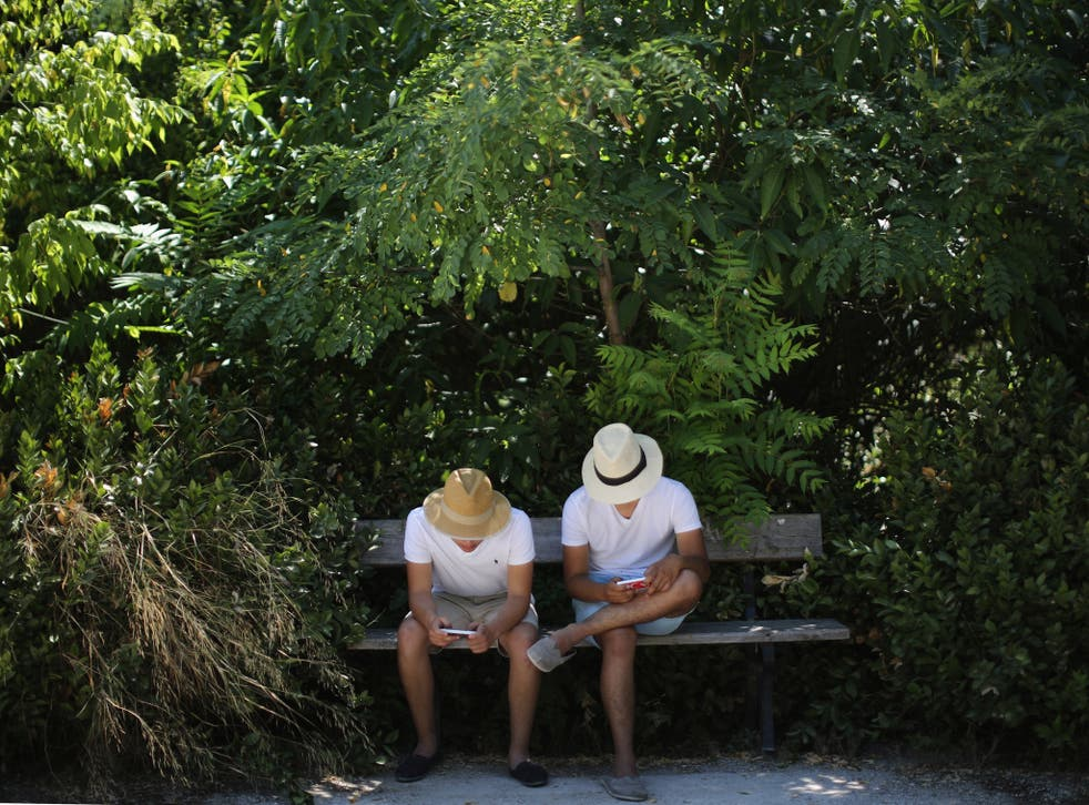 Two men look at their smart phones in the National Gardens on July 12, 2015 in Athens, Greece