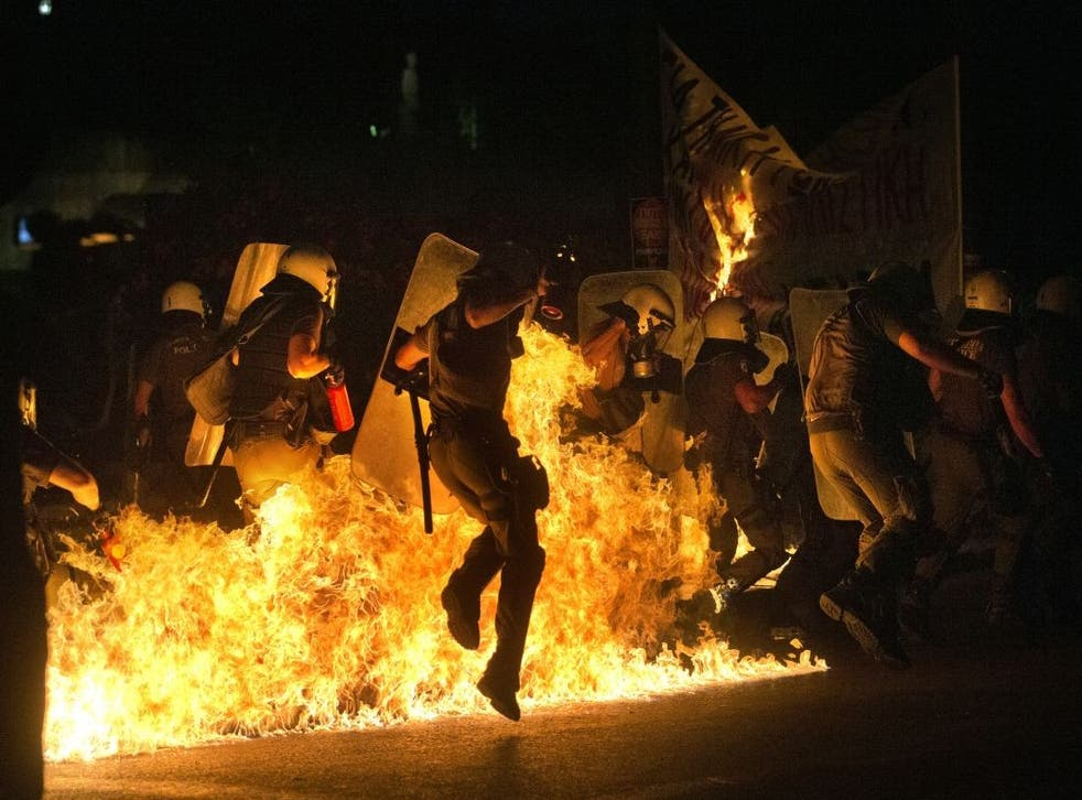 A police officer jumps to avoid fire from a petrol bomb thrown by anti-austerity protesters