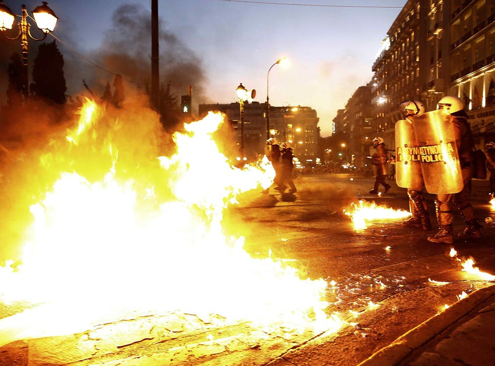 Riot police stand amongst the flames from exploded petrol bombs thrown by a small group of anti-establishment demonstrators in front of parliament in Athens, Greece July 15, 2015