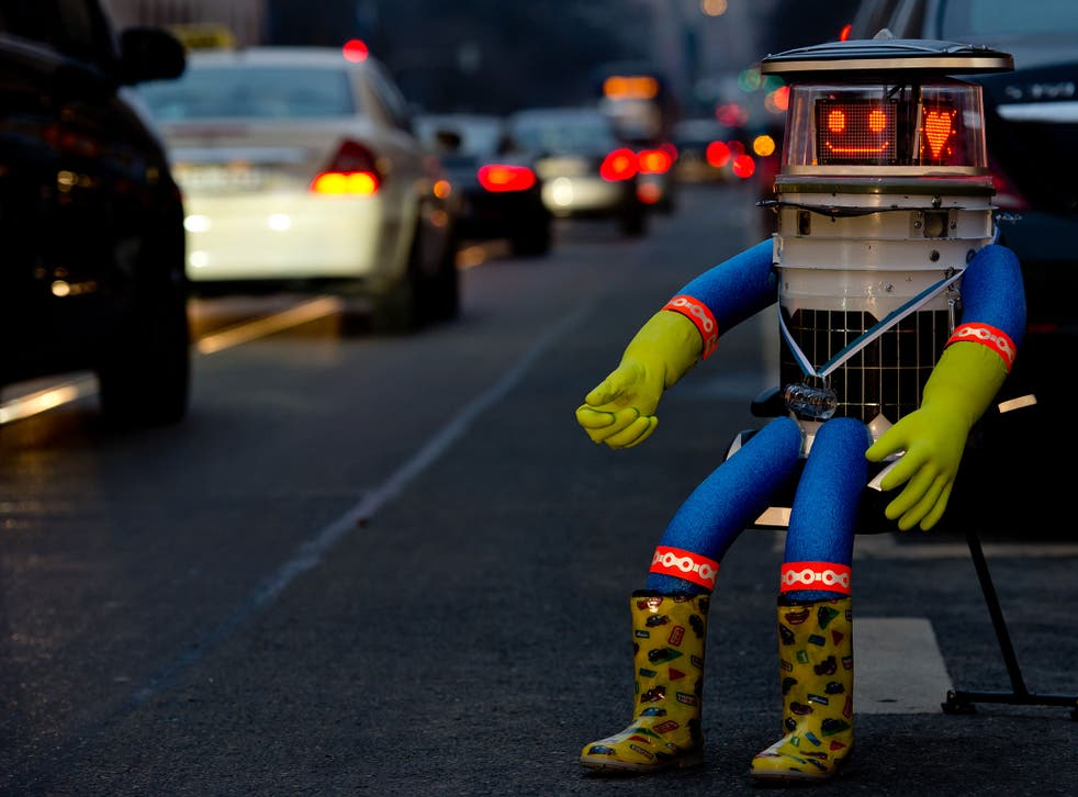 A robot called 'hitchBOT' sits on the side of a road and shows a smiling 'face' display