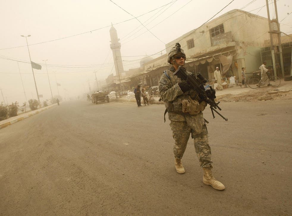 US soldiers and Iraqi police take part in their last joint patrol in Khan Bani Saad, some 10 kms south of the town of Baquba, on June 28 2009, as a sandstorm engulfs this northeastern region of the county. US combat troops will pull out from Iraq's cities