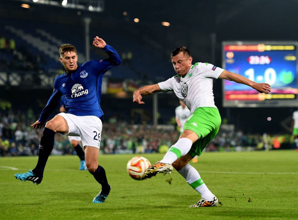 Ivica Olic of VfL Wolfsburg crosses the ball as John Stones of Everton closes in during a UEFA Europa League Group H match