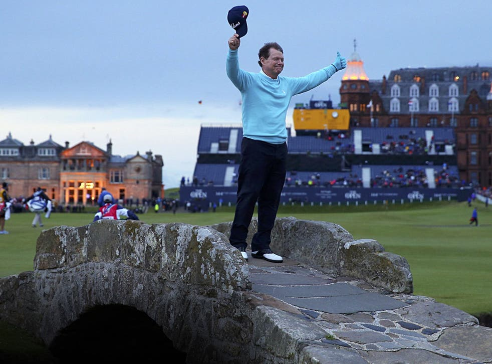 Five-time champion Tom Watson waves a poignant goodbye in the twilight on the Swilcan Bridge