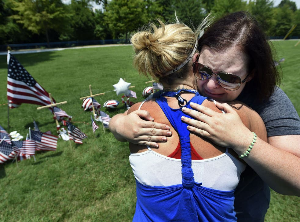 Sophia Ensley, left, comforts Barbie Branum by a makeshift memorial at the Marine Reserve Center in Chattanooga, Tennessee