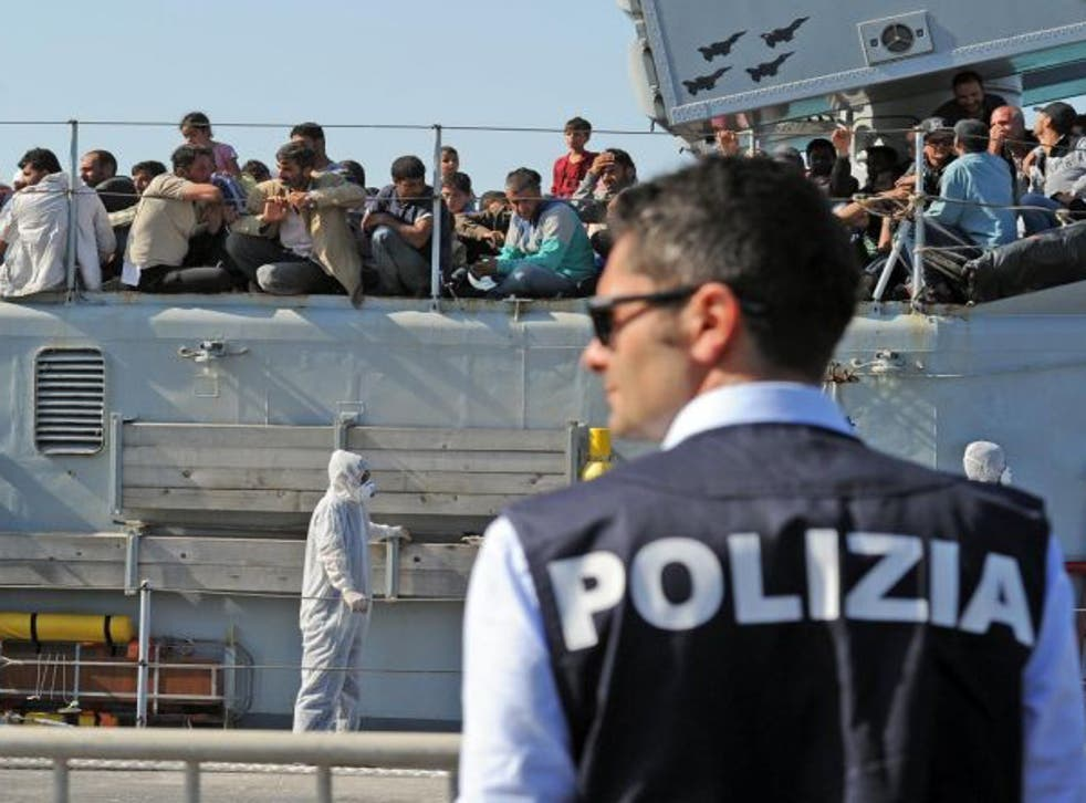 An Italian policeman stands guard as migrants wait and see if they'll be let ashore