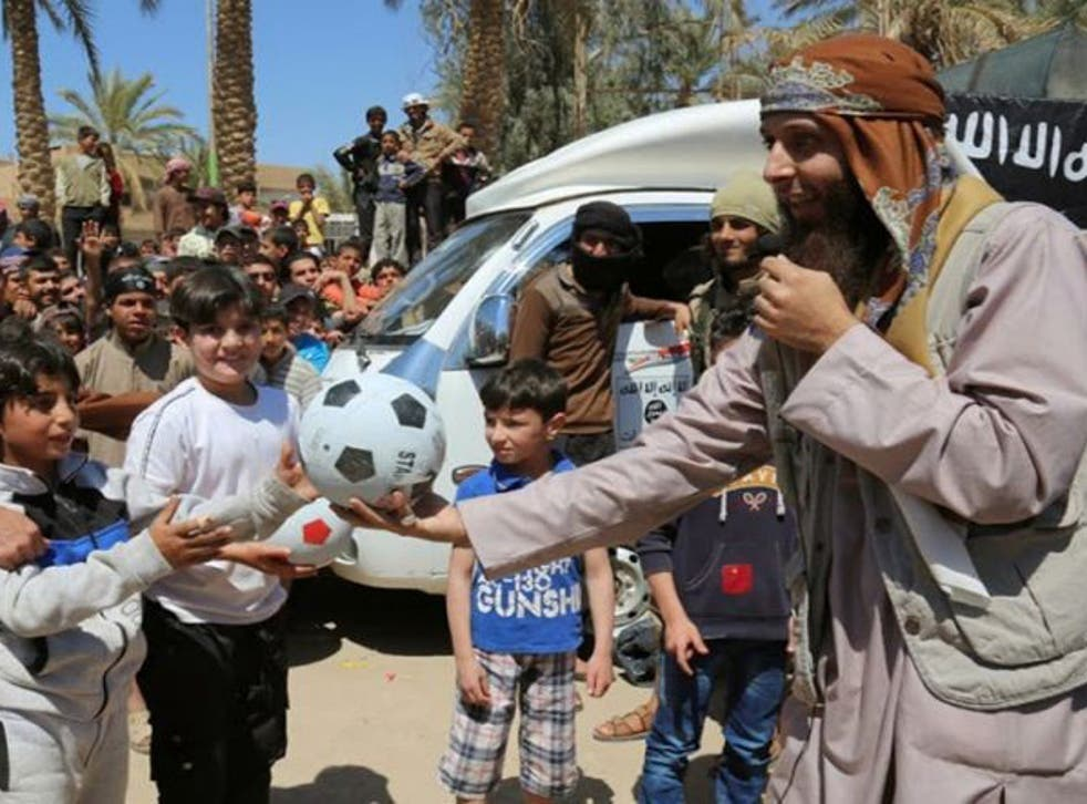 In an undated photo published by an Isis website, a jihadi fighter is see giving a boy a football during a street preaching event in Raqqa province, northern Syria