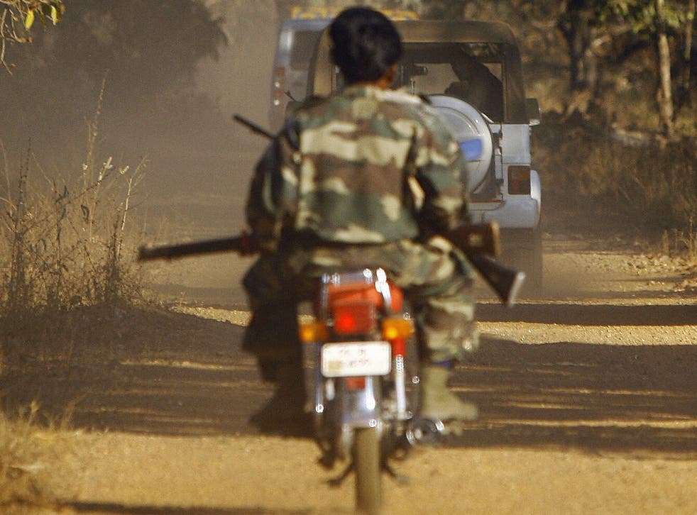A jeep carrying villagers waits for a convoy comprised of paramilitary forces and Special Police Officers