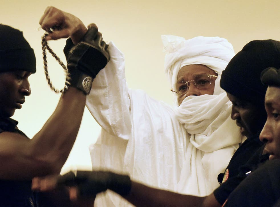 Former Chadian dictator Hissene Habre is escorted by prison guards into the courtroom for the first proceedings of his trial by the Extraordinary African Chambers in Dakar on July 20, 2015