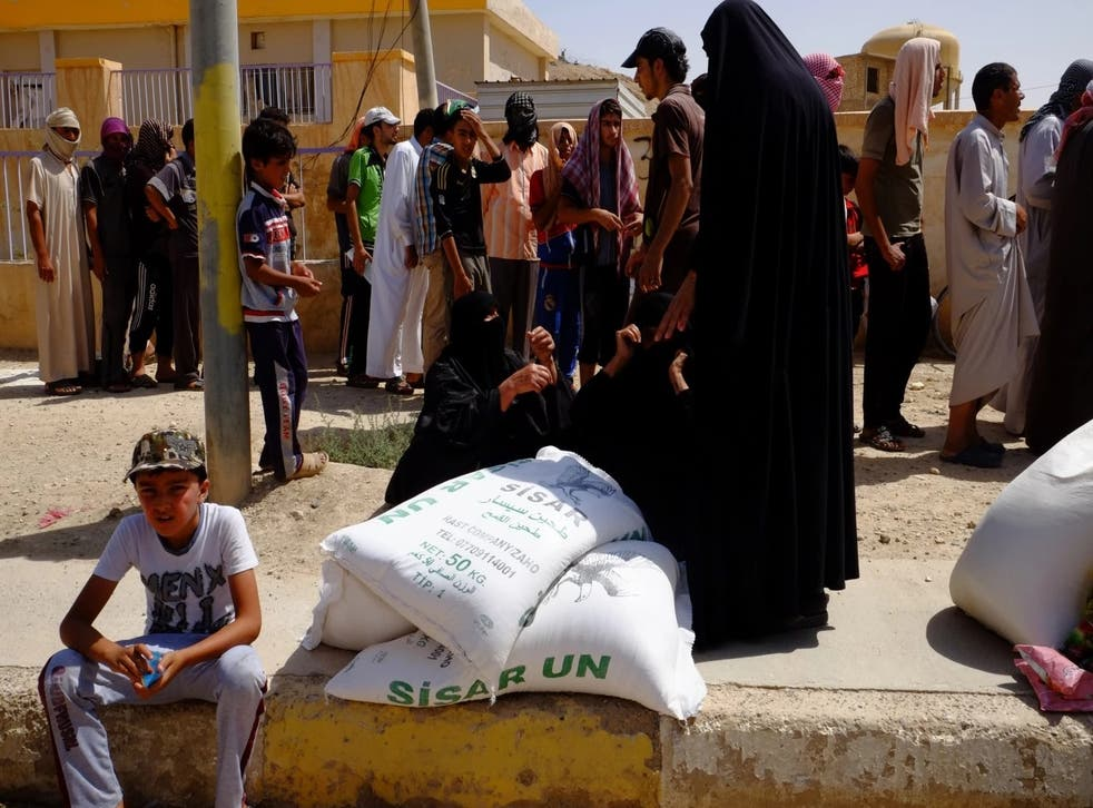 Families in Haditha receive sacks of flour in a food aid delivery July 16. Prices of food and gasoline have skyrocketed in the town after supply routes were cut off