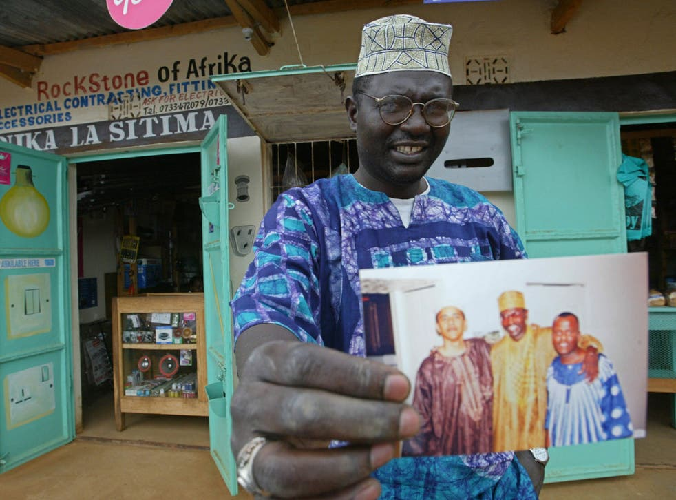 Malik Obama, the older brother of Barack, holds an undated picture outside his shop in Siaya in eastern Kenya