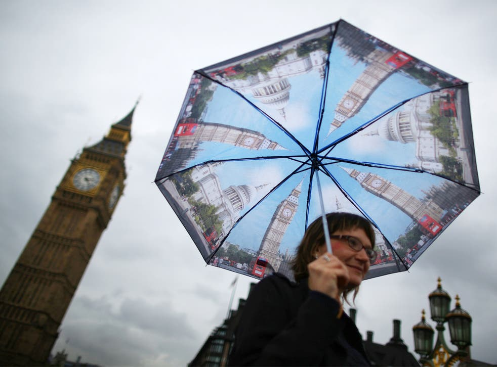 A visitor shelters from the rain under an umbrella decorated with images of Big Ben and St Paul's as she walks near Parliament in London. Downpours are being experienced in parts of the United Kingdom