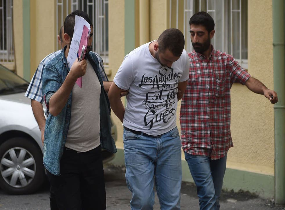 Turkish plain clothes police officers escort a suspected member of the Islamic State (IS) group at a hospital for a medical check-up on July 24