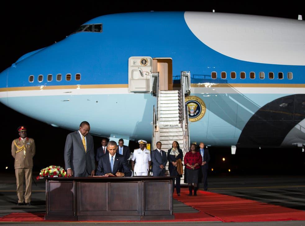 Kenyan President Uhuru Kenyatta, left, watches as President Barack Obama signs a guest book after arriving at Kenyatta International Airport