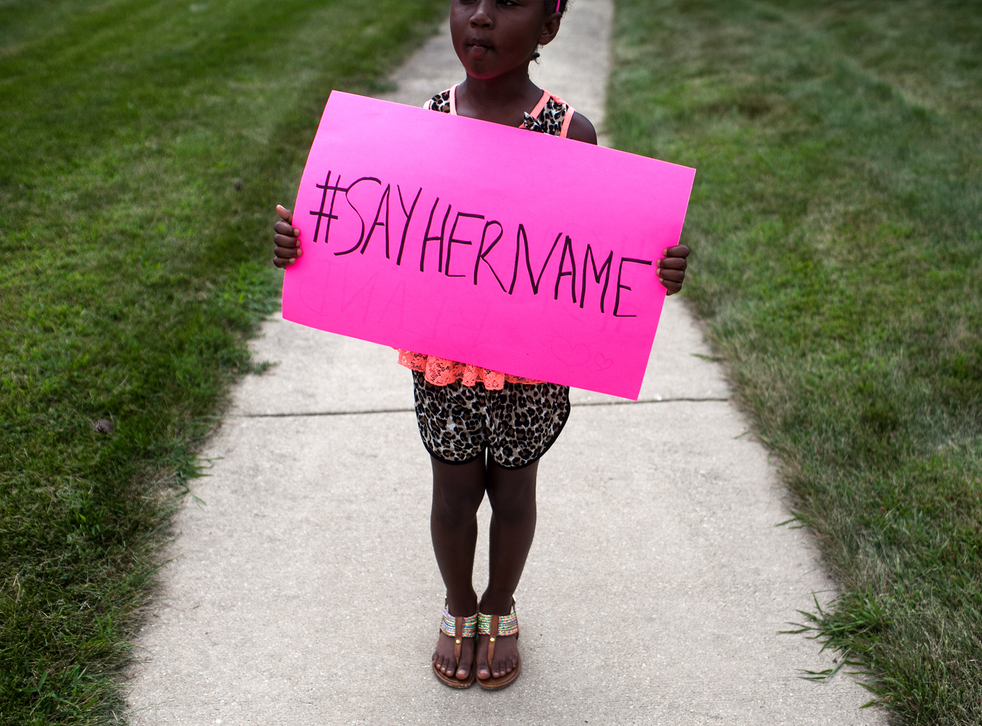 A young girl holds a sign in front of the DuPage African Methodist Episcopal Church during the funeral service for Sandra Bland