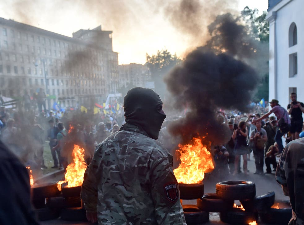 A far-right activist stands in front of a blaze of tyres near the Ukrainian government building in central Kiev