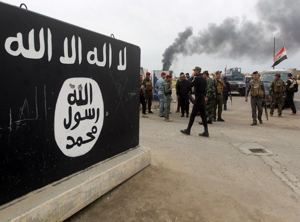 Iraqi security forces and Shiite fighters from the Popular Mobilisation units gather next to a mural depicting the emblem of Isis