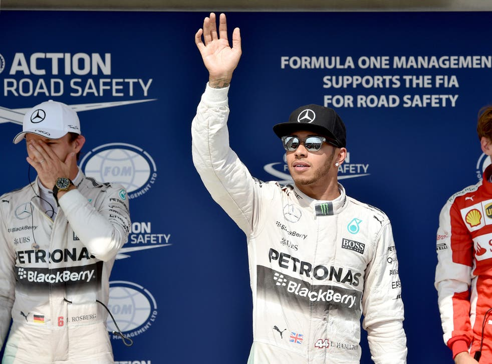 Nico Rosberg grimaces as Lewis Hamilton waves to the crowd