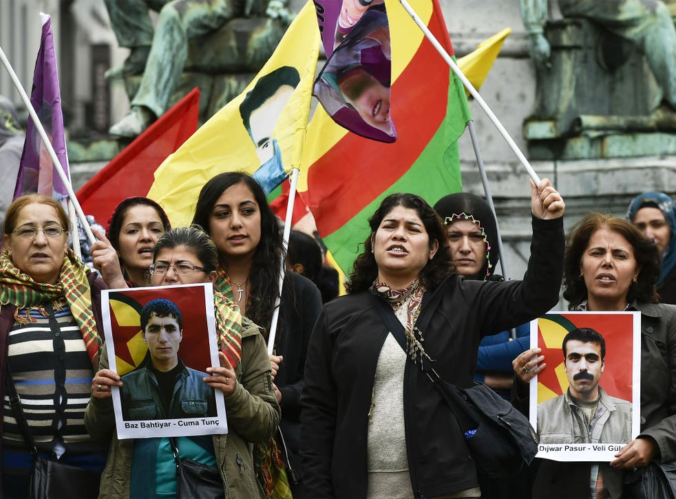Demonstrators in Brussels on Tuesday holding pictures of the victims of a suicide bombing in the Turkish town of Suruc last week