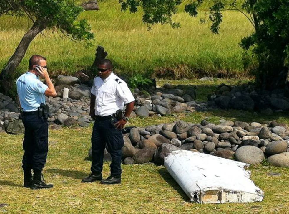 A policeman and a gendarme stand next to a piece of debris from an unidentified aircraft found in the coastal area of Saint-Andre de la Reunion, in the east of the French Indian Ocean island of La Reunion.