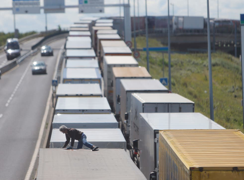 A driver climbs on his truck as he waits to cross the English channel, in Calais