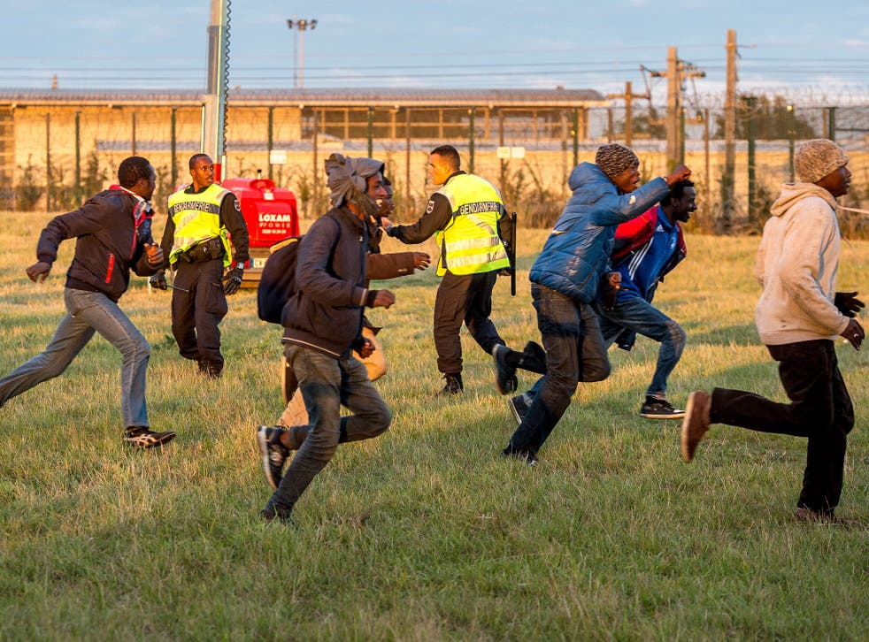 Migrants trying to reach the Channel Tunnel run past policemen in Coquelles near Calaisa