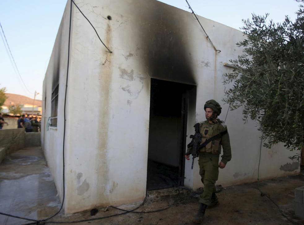 An Israeli soldier walks past a house that had been torched in a suspected attack by Jewish extremists