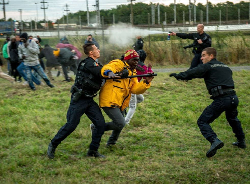 Channel clash: a migrant is held back by French police at the Eurotunnel site