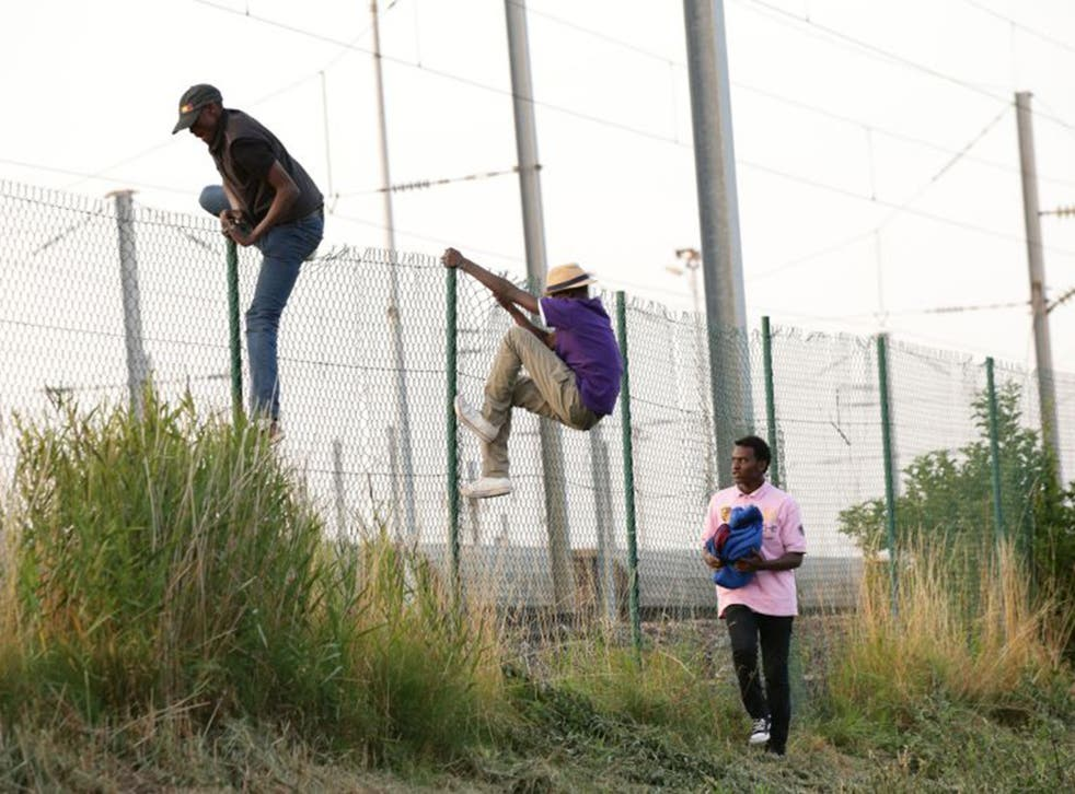 Migrants climb over a fence onto the tracks near the Eurotunnel site at Coquelles in Calais (PA)