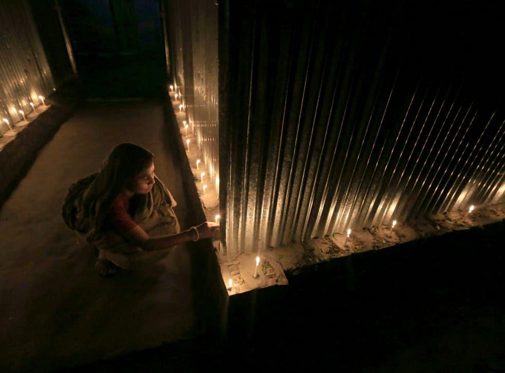 A woman lights candles in celebration at Dashiarchhara, Bangladesh.
