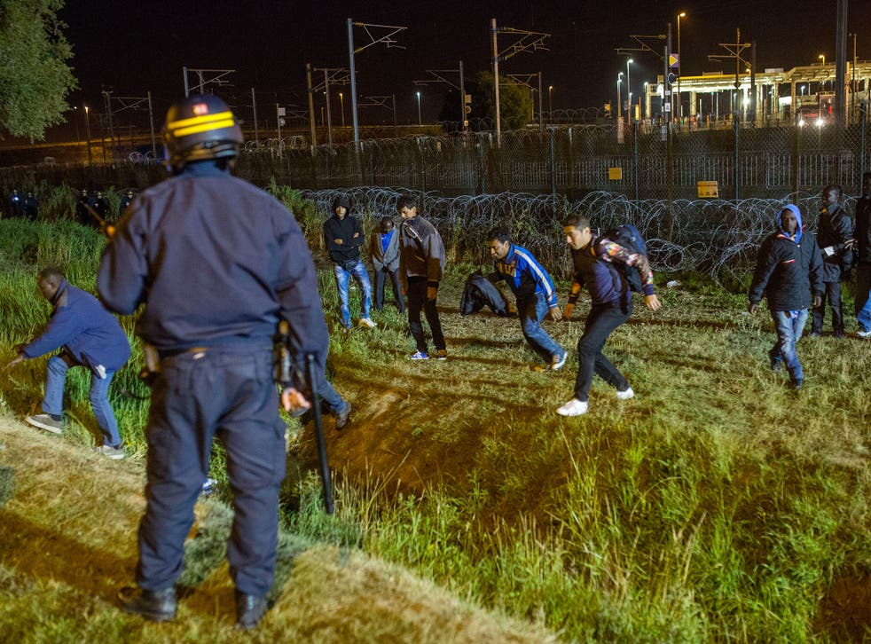 A policeman watches men move away from a security fence beside train tracks near the Eurotunnel terminal in Coquelles