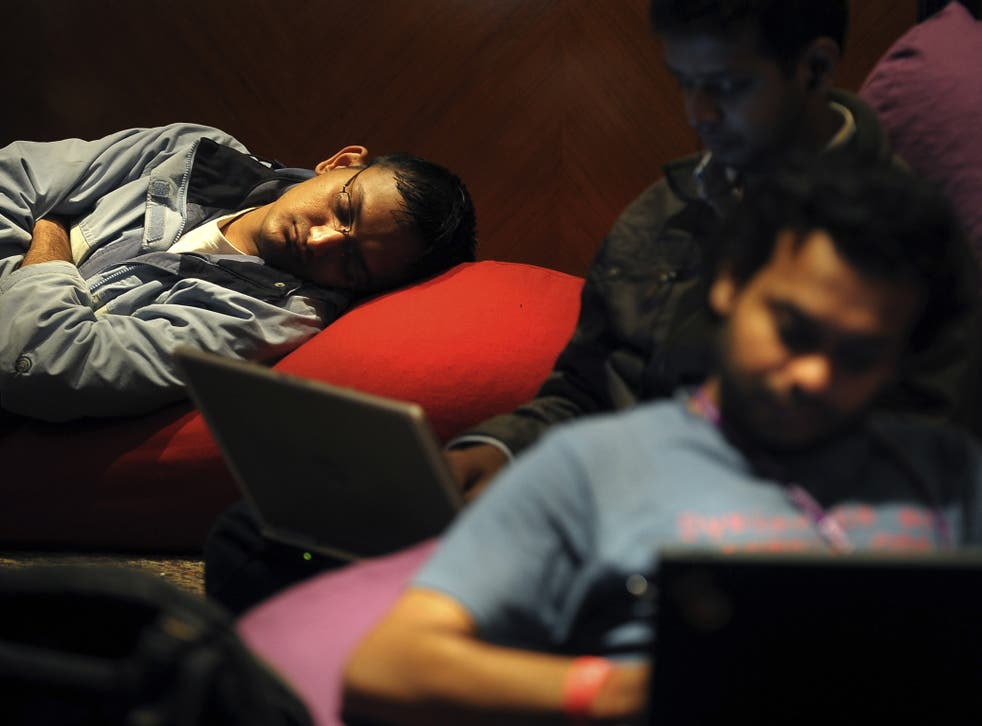 Indian IT professionals work on their laptops as others sleep during an 'Open Hack Day' programme organised by the global search engine Yahoo! in Bangalore on July 25, 2010