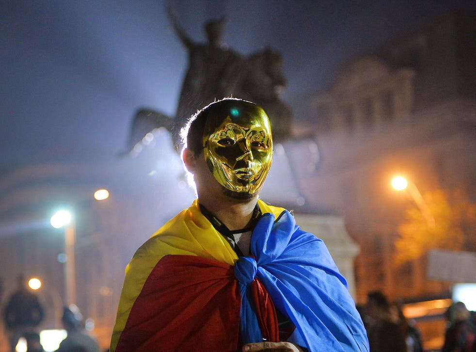 A protester wears a golden mask and Romanian flag during a demonstration in Bucharest against Gabriel Resources Rosia Montana gold and silver project