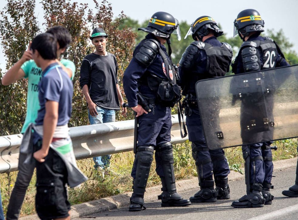 French riot police try to prevent migrants from reaching the road leading to Calais' ferry port