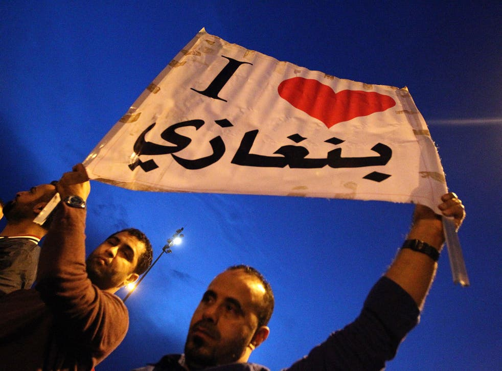 "Protesters raise up a placard reading in Arabic ""I love Benghazi"" during a demonstration in front of the Tibesti hotel in support of the Libyan Army and Police"