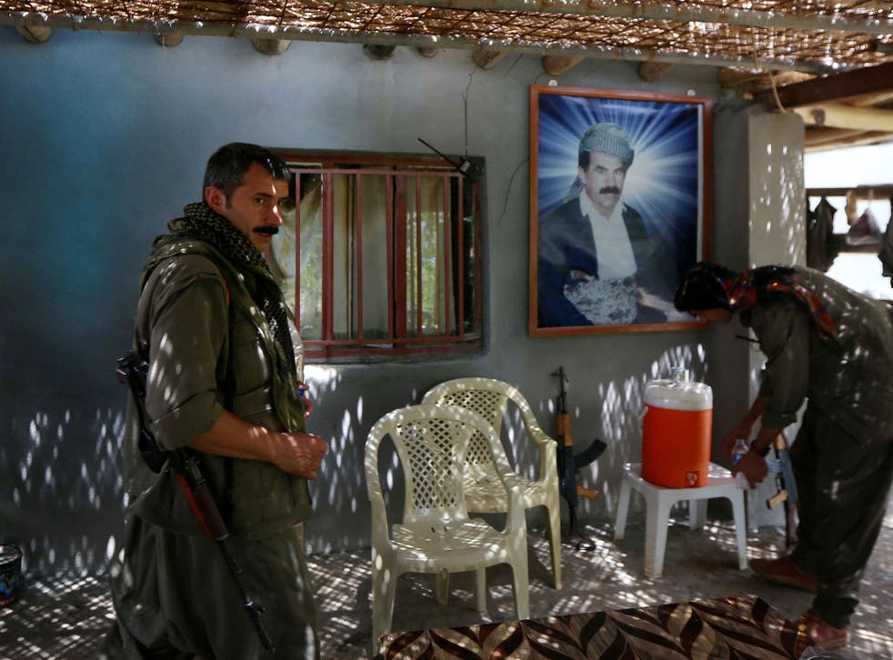 Members of the Kurdistan Workers' Party (PKK) rest in front of a portrait of jailed Kurdish rebel chief Abdullah Ocalan at a camp on July 29, 2015
