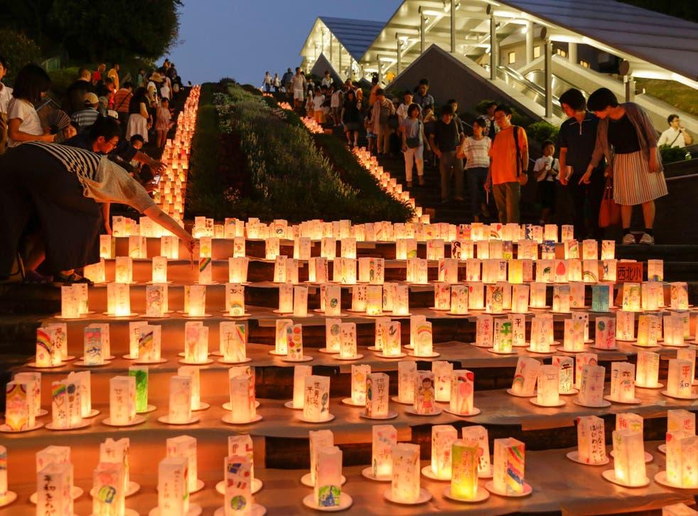 Visitors look at paper lanterns displayed for the Peace Candle Lights at Nagasaki Peace Park (EPA)